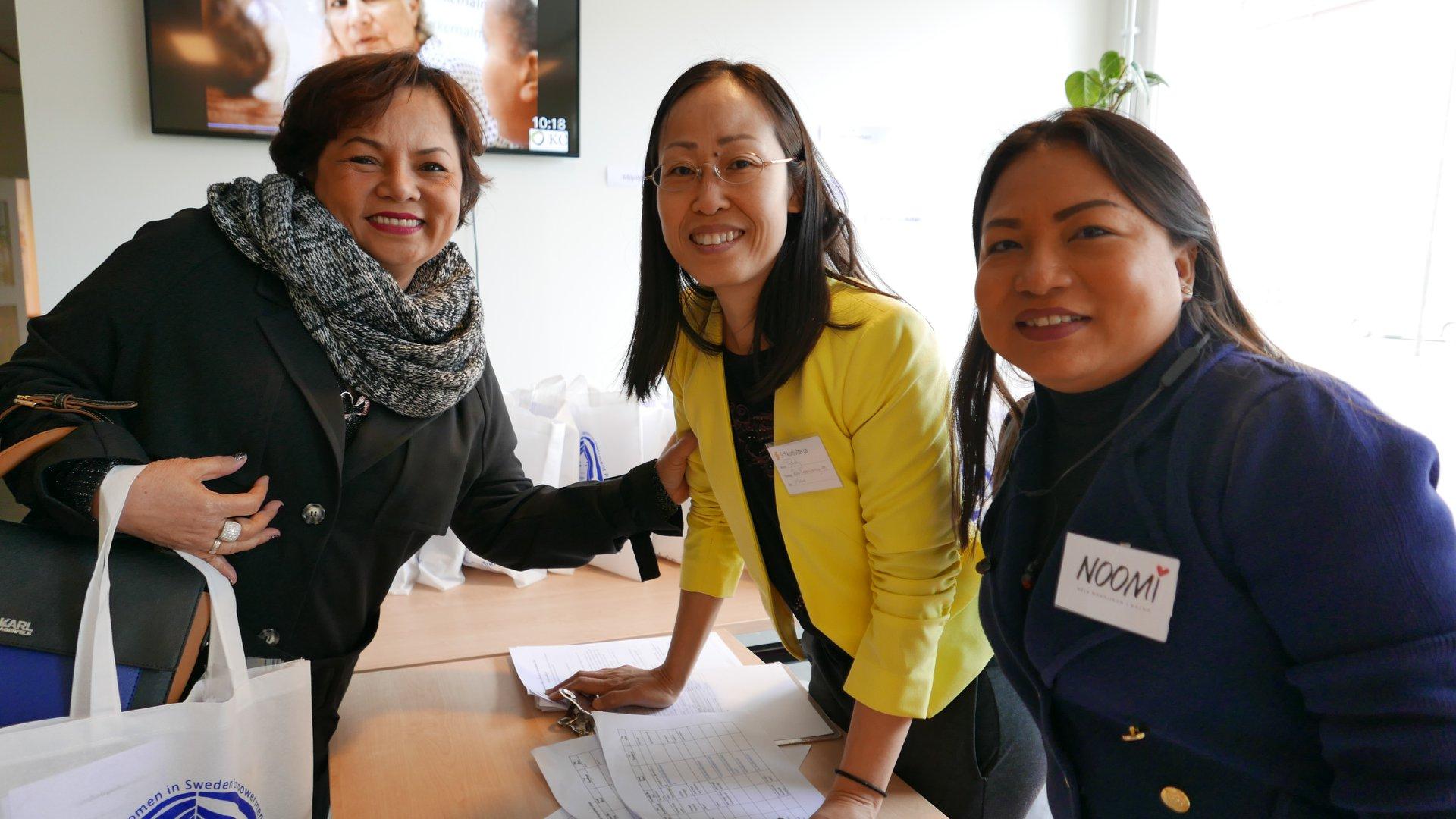 ผู้หญิงสามคนกำลังยืนถ่ายรูปที่โต๊ะ
