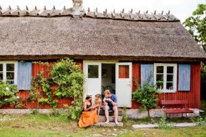 พ่อแม่ลูกนั่งหน้าบ้านกำลังกินขนมกัน
